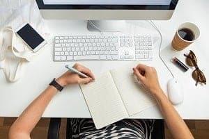 n, die am Schreibtisch sitzt und mit der linken Hand einen Stift hält - Shop Startseite