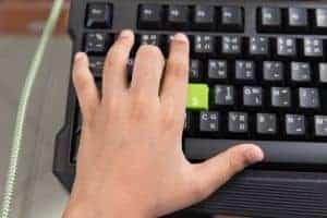 Linke Hand eines Computernutzers auf einer Tastatur