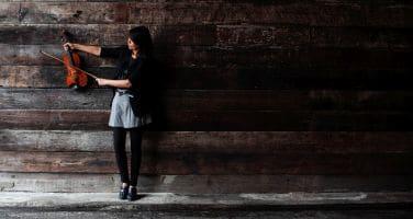 Eine Frau steht an einer Wand und hat eine Geige in der Hand